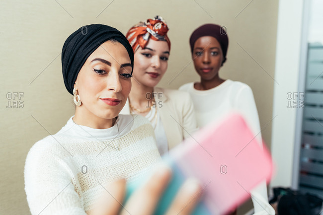 Woman taking selfie with colleagues