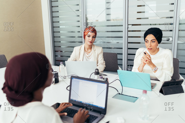 Three female colleagues working at shared desk