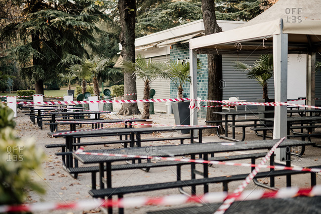 February 28, 2016: Cordon tape around seating outside cafe during 2020 Covid-19 Lockdown, Milan, Italy