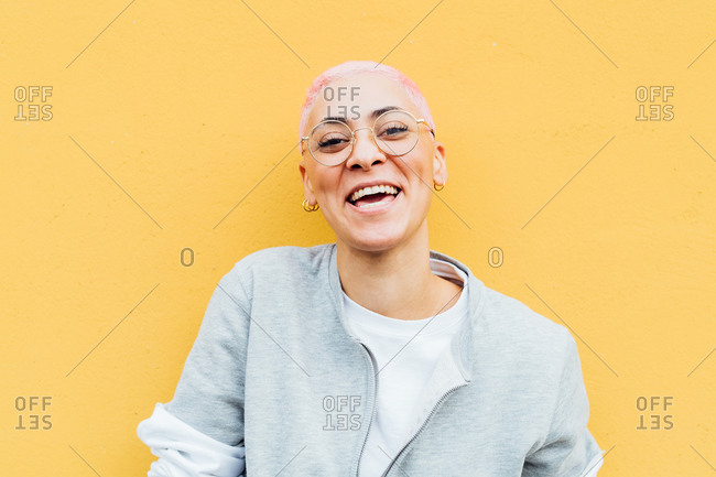 Portrait of happy young woman with short pink hair, wearing glasses