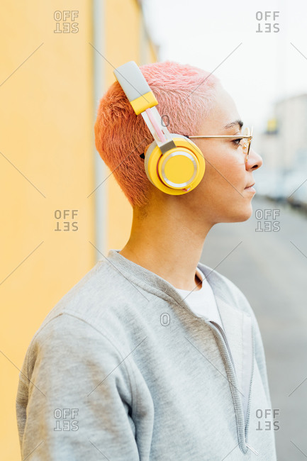 Portrait of woman with short pink hair, wearing headphones