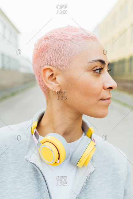 Portrait of young woman with short pink hair, wearing headphones