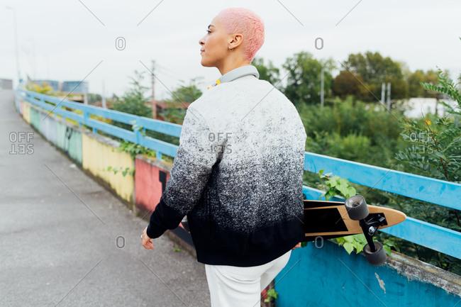 Skateboarder walking on a bridge