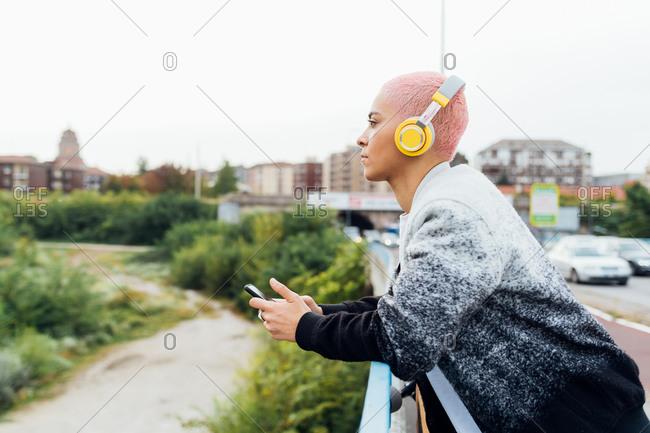 Woman on bridge, listening to music on headphones