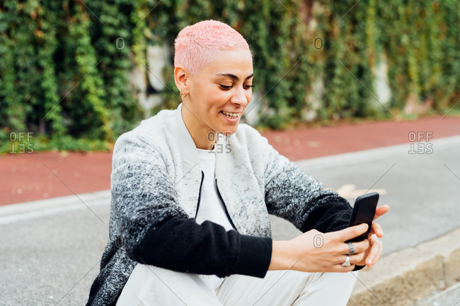 Young woman sitting on sidewalk, using cellphone