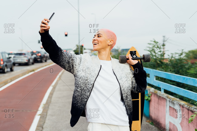 Skateboarder walking her using her cellphone