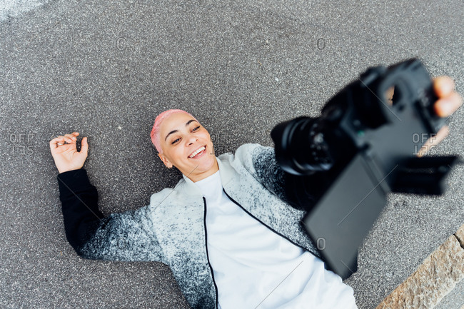 Photographer lying on ground and taking selfie with camera