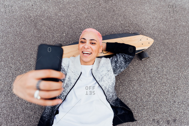 Skateboarder lying on board and using phone