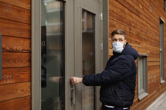 Man wearing face mask opening door