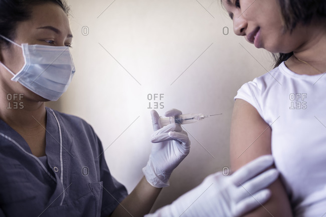 Woman receiving injection in her arm