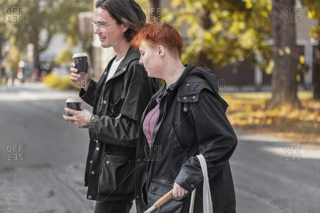 Visually impaired woman walking in street with male friend