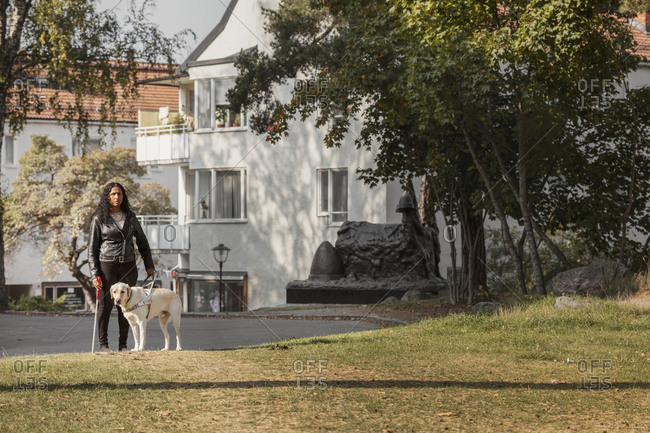 Visually impaired woman standing on lawn with guide dog