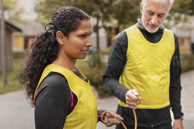 Visually impaired woman preparing for jogging with guide runner