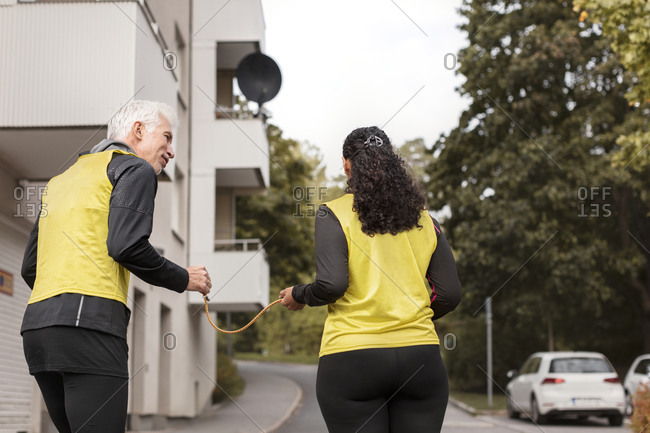 Visually impaired woman jogging with guide runner