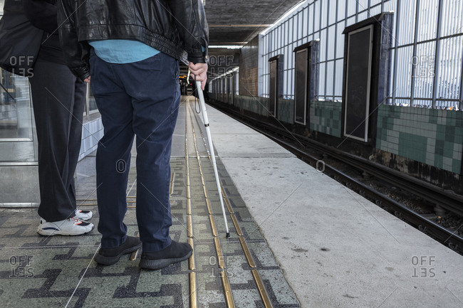 Man with white cane standing at train station
