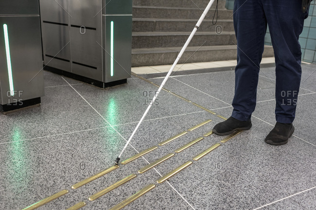 Low section of person with white cane standing at metro station