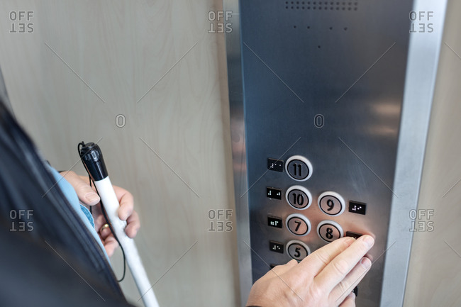 Person with white cane using elevator