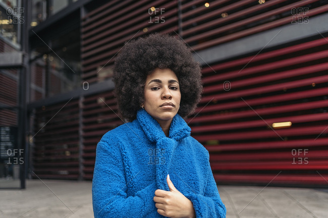 Expressive afro woman wearing cool blue coat looking at camera.