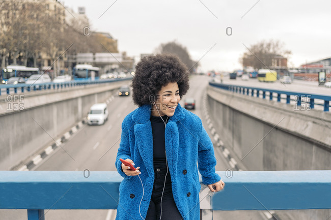 Beautiful african american girl smiling and using her smart-phone.