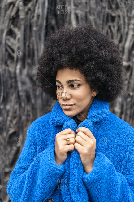 Young afro woman with expressive look looking away against black background.