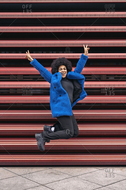 Beautiful african american girl jumping and making peace sign in the city.