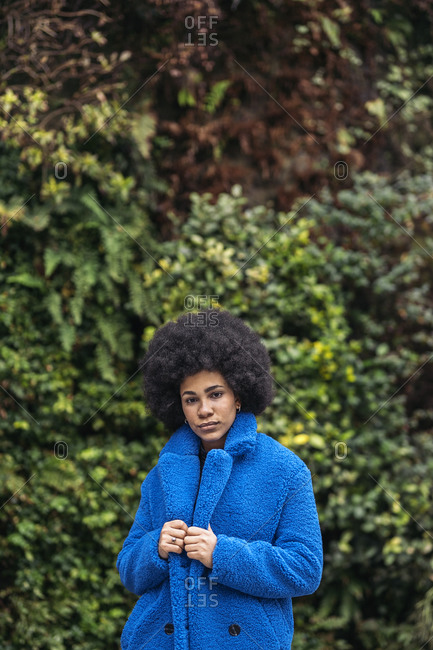 Young afro woman with expressive look against green background.