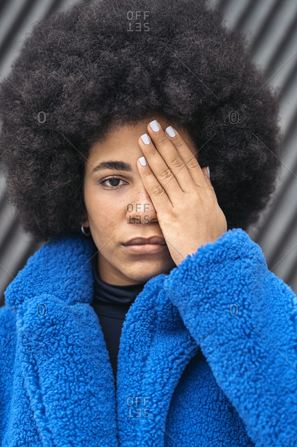 Expressive african american covering her face with her hand and looking at camera.