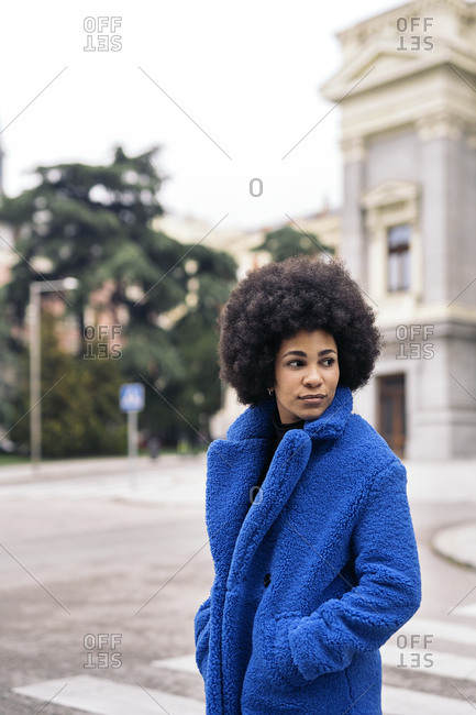 Young afro woman with expressive look walking in the city.