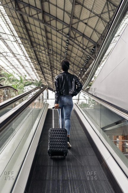 Unrecognized woman with suitcase going upstairs in mechanical ramp.