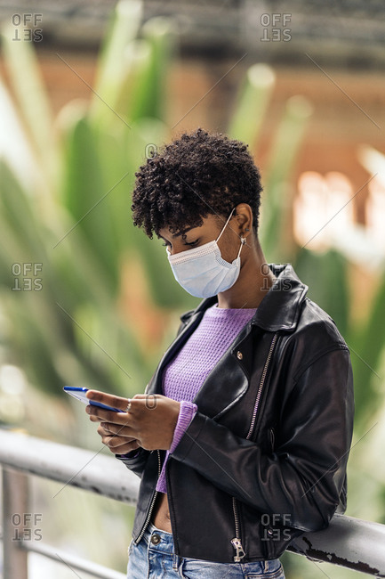 African girl wearing face mask using phone while waiting in train station.
