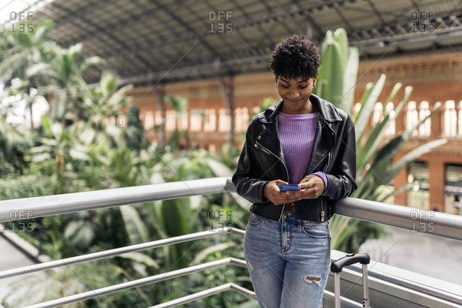 Happy african girl using phone while waiting in train station.