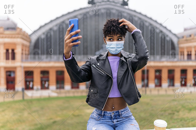 Beautiful african girl wearing face mask taking selfie in the streets of madrid.