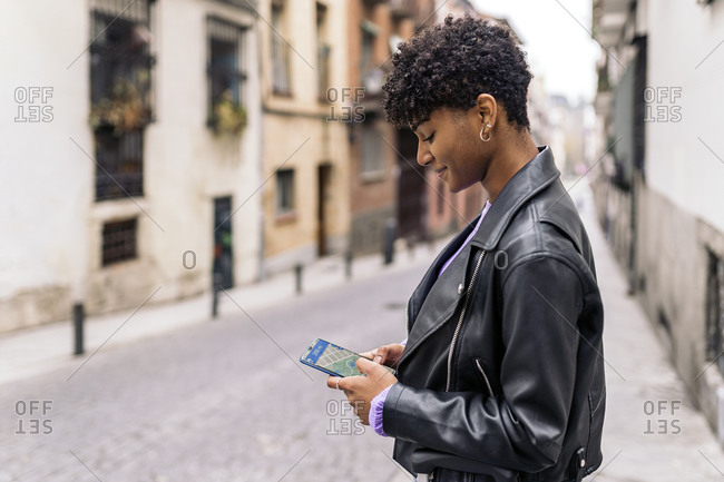 Young afro woman looking at a map in her phone.