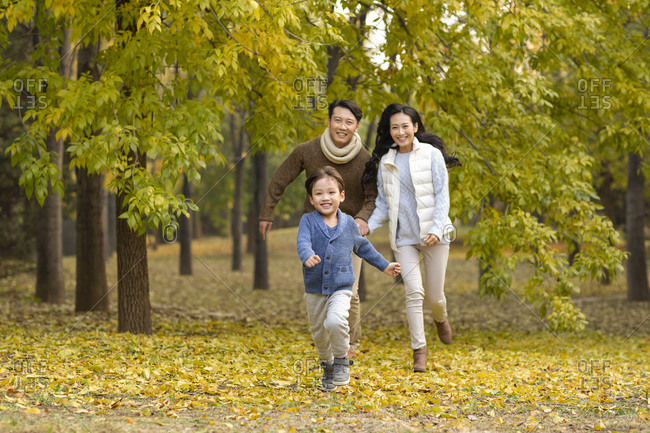 Happy young family running in woods
