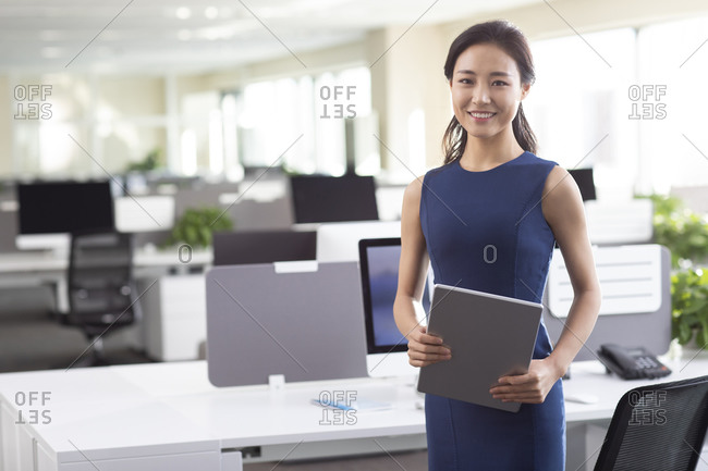 Confident businesswoman with digital tablet in office