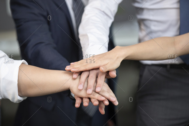 Business people stacking hands in office