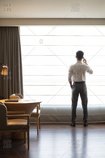Young businessman using smartphone in hotel room