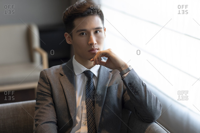 Young businessman sitting on sofa in hotel room