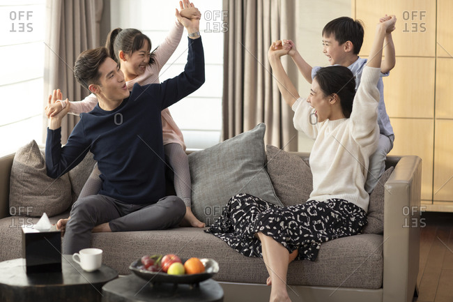 Happy young family having fun in living room