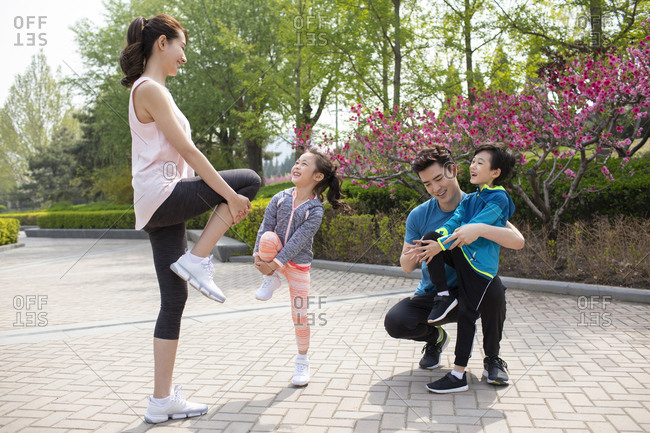 Happy young family exercising in park