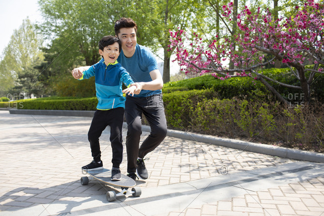 Father teaching his son to skateboard