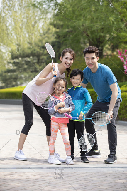 Happy young family playing badminton in park