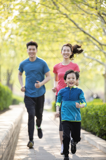 Happy young family running in park