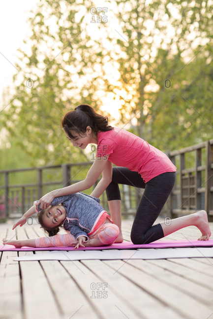 Happy mother and daughter doing yoga outdoors