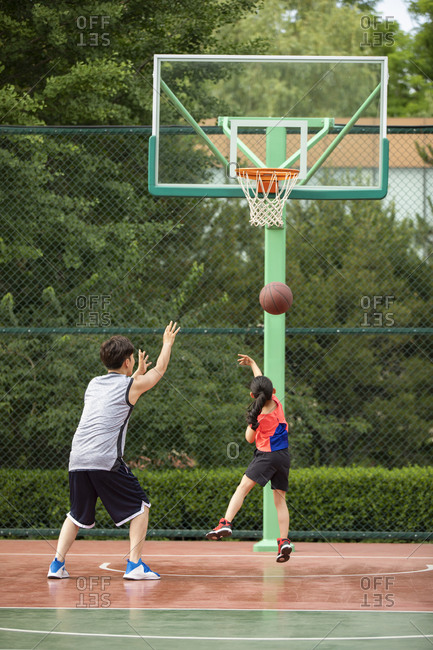 Father and daughter playing basketball on playground