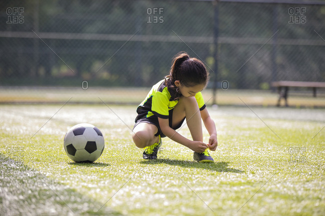 Little girl tying shoelace on soccer field