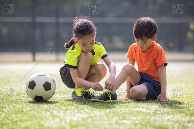 Little girl helping her brother to tie shoelace on soccer field