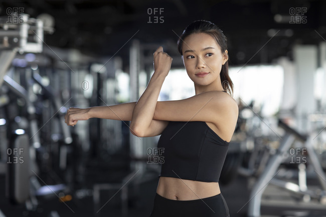 Young woman stretching at gym