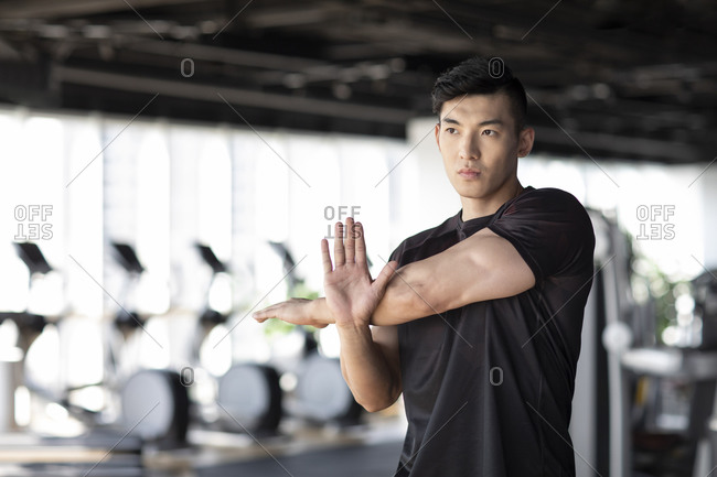 Young man stretching at gym