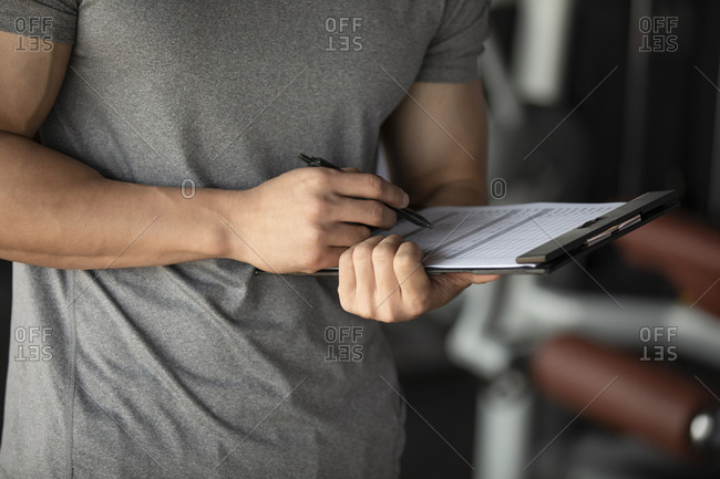 Young fitness instructor looking at chart, close up
